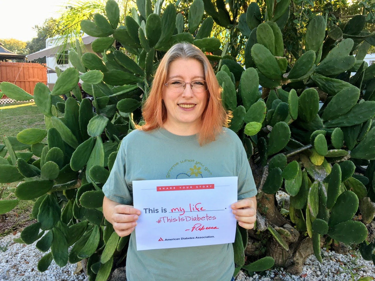 Rebecca Dugas holding sign in front of cactus