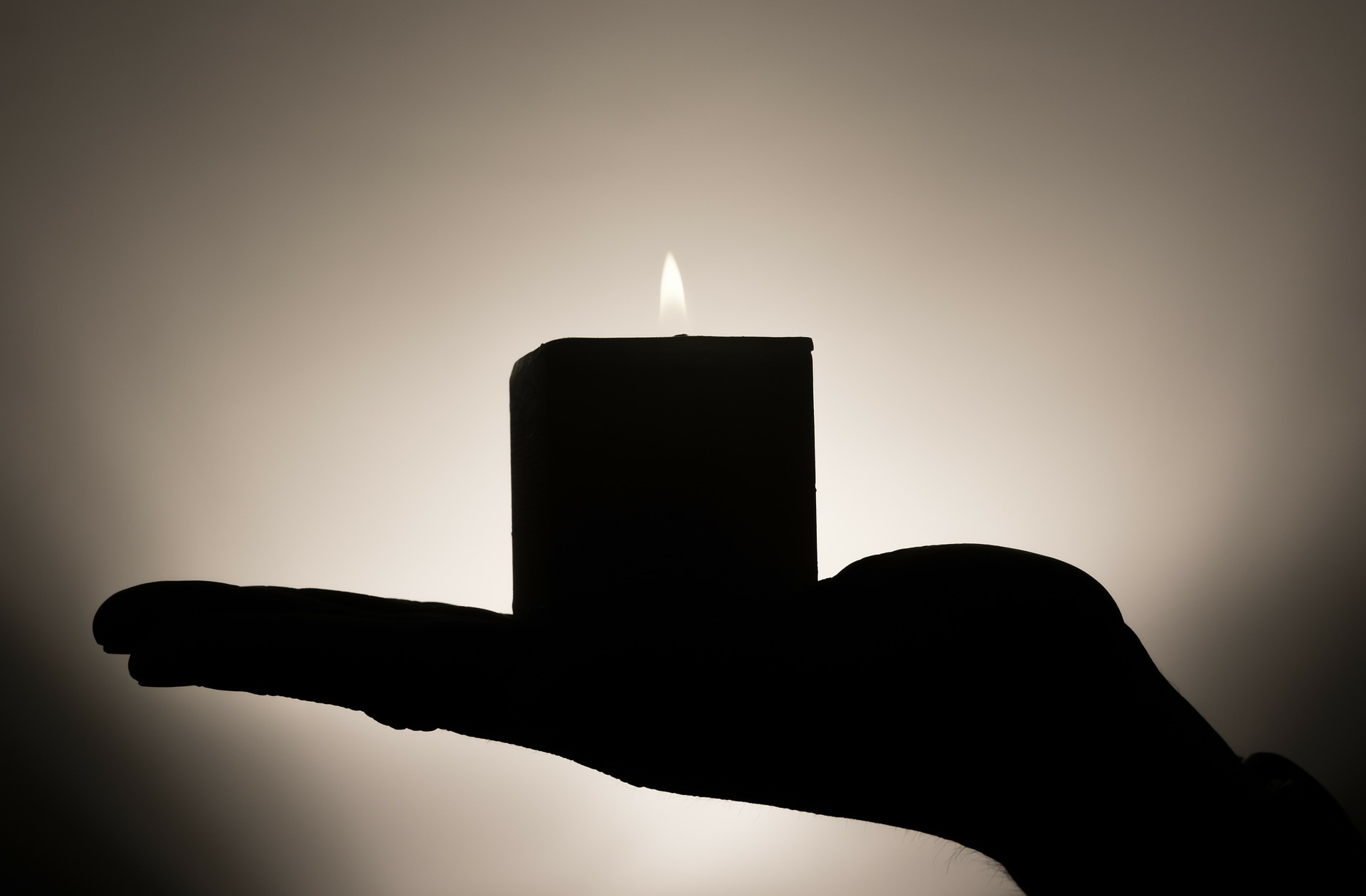 Silhouette of hand holding lit candle